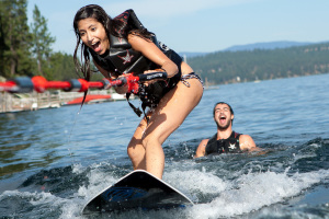 With the help of Josh Goldberg (right), Pamela Vasquez gets up on a wake surfboard for the first time on Lake Coeur d'Alene in northern Idaho.